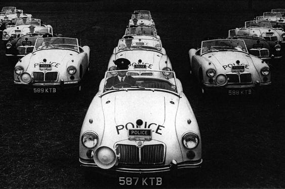 Slide 26 of 78: <p>The MGA carried on where the T-Series left off, in 1955. This shot from 1959 shows Lancashire Police showing off its 18 new MGAs, which were driven only by police drivers trained in the art of roadcraft.</p>