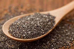 Wooden spoonful of chia seeds on table top. Shallow depth of field.