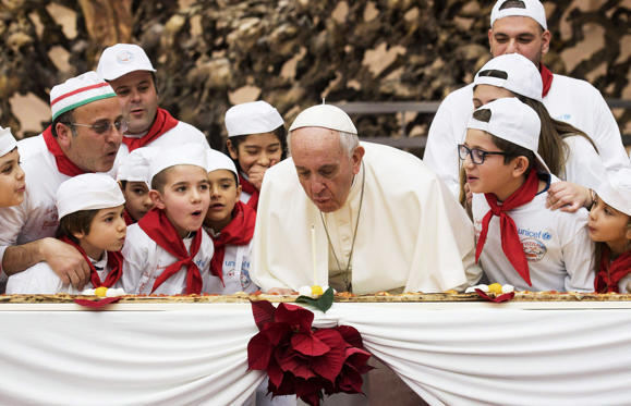 Slide 1 of 7: Pope Francis blows a candle on the occasion of his 81st birthday during a private audience with children the Paul VI hall at the Vatican, Sunday, Dec. 17, 2017.