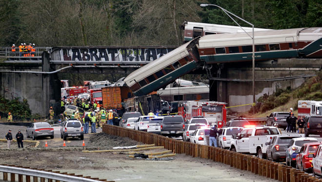 Slide 7 of 15: Cars from an Amtrak train lay spilled onto Interstate 5 below as some remain on the tracks above Monday, Dec. 18, 2017, in DuPont, Wash. The Amtrak train making the first-ever run along a faster new route hurtled off the overpass Monday near Tacoma and spilled some of its cars onto the highway below, killing some people, authorities said. Seventy-eight passengers and five crew members were aboard when the train moving at more than 80 mph derailed about 40 miles south of Seattle before 8 a.m., Amtrak said. (AP Photo/Elaine Thompson)