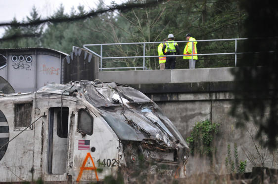 Slide 3 of 15: First responders are seen at the scene of an Amtrak passenger train which derailed and is hanging from a bridge over the interstate highway (I-5) in DuPont, Washington, U.S., December 18, 2017.    REUTERS/Tom James - RC1178944F40