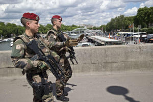 French soldiers of the 'Operation Sentinelle' walk on the Mirabeau bridge on May 20, 2017 in Paris.