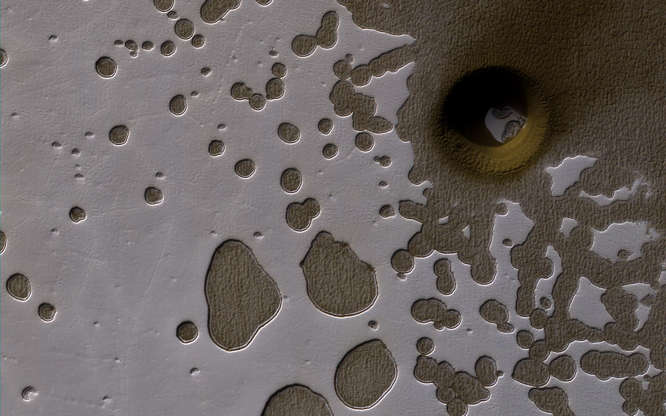 Slide 18 of 86: A late summer view of the Southern hemisphere of Mars seen in this image from NASA's Mars Reconnaissance Orbiter released on June 2. Shallow pits are seen in the bright residual cap of carbon dioxide ice. There is also a deeper, circular formation that penetrates through the ice and dust, possibly an impact crater or a collapse pit.