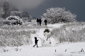 A child plays in the snow next to a snow man, by the road called route de la Gineste, connecting Marseille and Cassis, on December 2, 2017, outside Marseille, southern France.