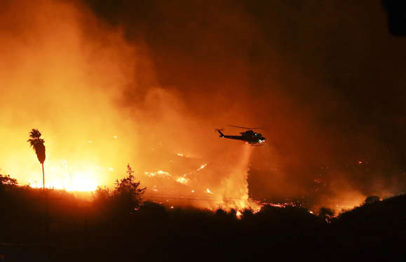 Slide 3 of 75: A helicopter drops water over a wildfire on Dec. 7 in Bonsall, Calif