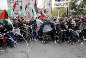 Protesters try to remove barbed wires that block a road leading to the U.S. embassy during a demonstration in Aukar, east of Beirut, Lebanon, Sunday, Dec. 10, 2017. Scores of demonstrators, including Palestinians, pelted security outside the embassy with stones and burned an effigy of U.S. President Donald Trump in a protest to reject Washington's recognition of Jerusalem as capital of Israel.