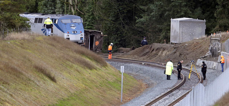Slide 6 of 15: Cars from an Amtrak train remain on the tracks above where other cars spilled below onto Interstate 5 Monday, Dec. 18, 2017, in DuPont, Wash. The Amtrak train making the first-ever run along a faster new route hurtled off the overpass Monday near Tacoma and spilled some of its cars onto the highway below, killing some people, authorities said. Seventy-eight passengers and five crew members were aboard when the train moving at more than 80 mph derailed about 40 miles south of Seattle before 8 a.m., Amtrak said. (AP Photo/Elaine Thompson)