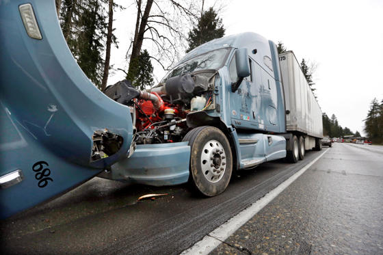 Slide 5 of 15: A semi-truck with visible damage to its hood sits parked on the shoulder just ahead of a car covered in mud and debris and with a smashed windshield just beyond where an Amtrak train lay spilled onto Interstate 5 below as some train cars remain on the tracks above Monday, Dec. 18, 2017, in DuPont, Wash. The Amtrak train making the first-ever run along a faster new route hurtled off the overpass Monday near Tacoma and spilled some of its cars onto the highway below, killing some people, authorities said.  (AP Photo/Elaine Thompson)