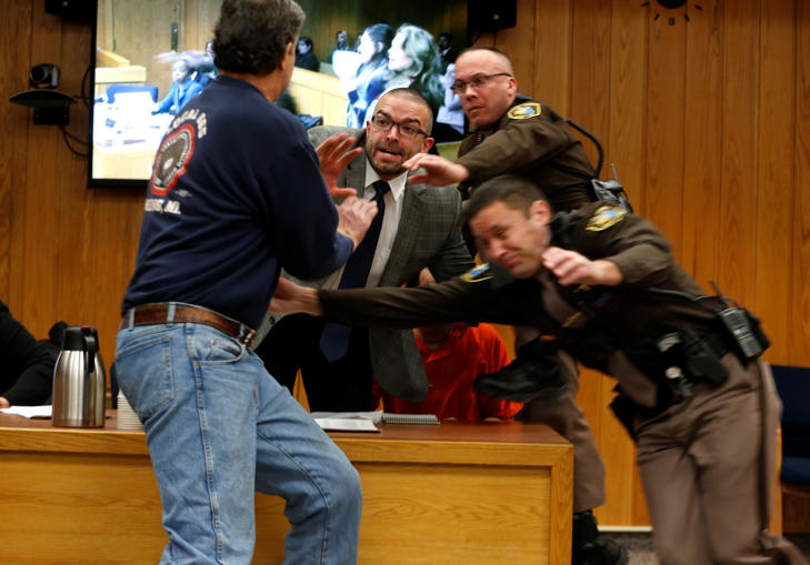 Randall Margraves (L) lunges at Larry Nassar,(wearing orange) a former team USA Gymnastics doctor who pleaded guilty in November 2017 to sexual assault charges, during victim statements of his sentencing in the Eaton County Circuit Court in Charlotte, Michigan, U.S., February 2, 2018