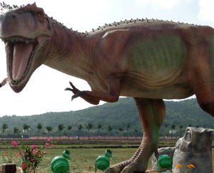 A visitors poses with a dinosaur model at Haitang Bay Rice Paddy Park on January 24, 2018 in Sanya, Hainan Province of China. The Haitang Bay Rice Paddy Park featuring 323 full-size dinosaur models was officially opened to the public on Thursday.