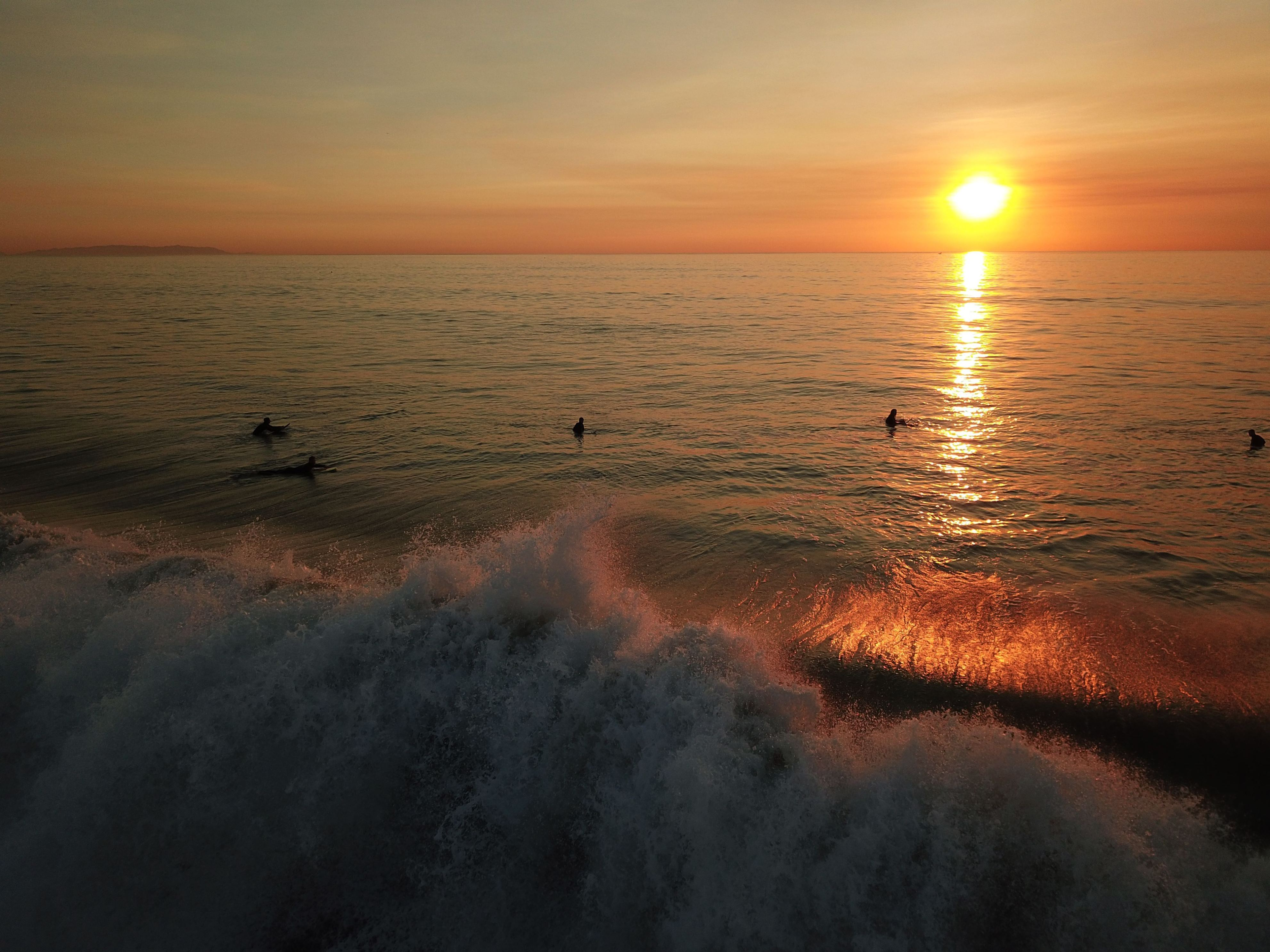 Slide 2 of 73: An aerial picture taken with a drone shows surfers waiting to catch a wave in Manhattan Beach, California, USA, 15 December 2017. Record high temperatures and high winds have caused red flag warnings across the area.