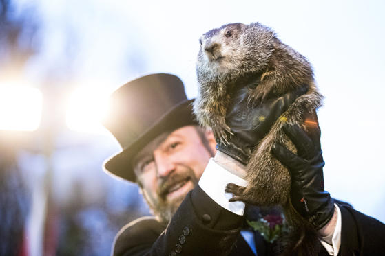 Slide 1 of 36: Punxsutawney Phil is held up by his handler for the crowd to see during the ceremonies for Groundhog day on Feb. 2, in Punxsutawney, Pennsylvania. Phil predicted six more weeks of winter after seeing his shadow. Groundhog Day is a popular tradition in the United States and Canada where people await the sunrise and the groundhog's exit from his winter den. If Punxsutawney Phil sees his shadow he regards it as an omen of six more weeks of bad weather and returns to his den. Early spring arrives if he does not see his shadow, causing Phil to remain above ground.