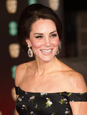 Catherine, Duchess of Cambridge, wearing a black off-the shoulder Alexander McQueen gown adorned with white flowers and large glittering earrings, arriving at the BAFTA Awards, held at the Royal Albert Hall, Kensington Gore, Kensington, London.