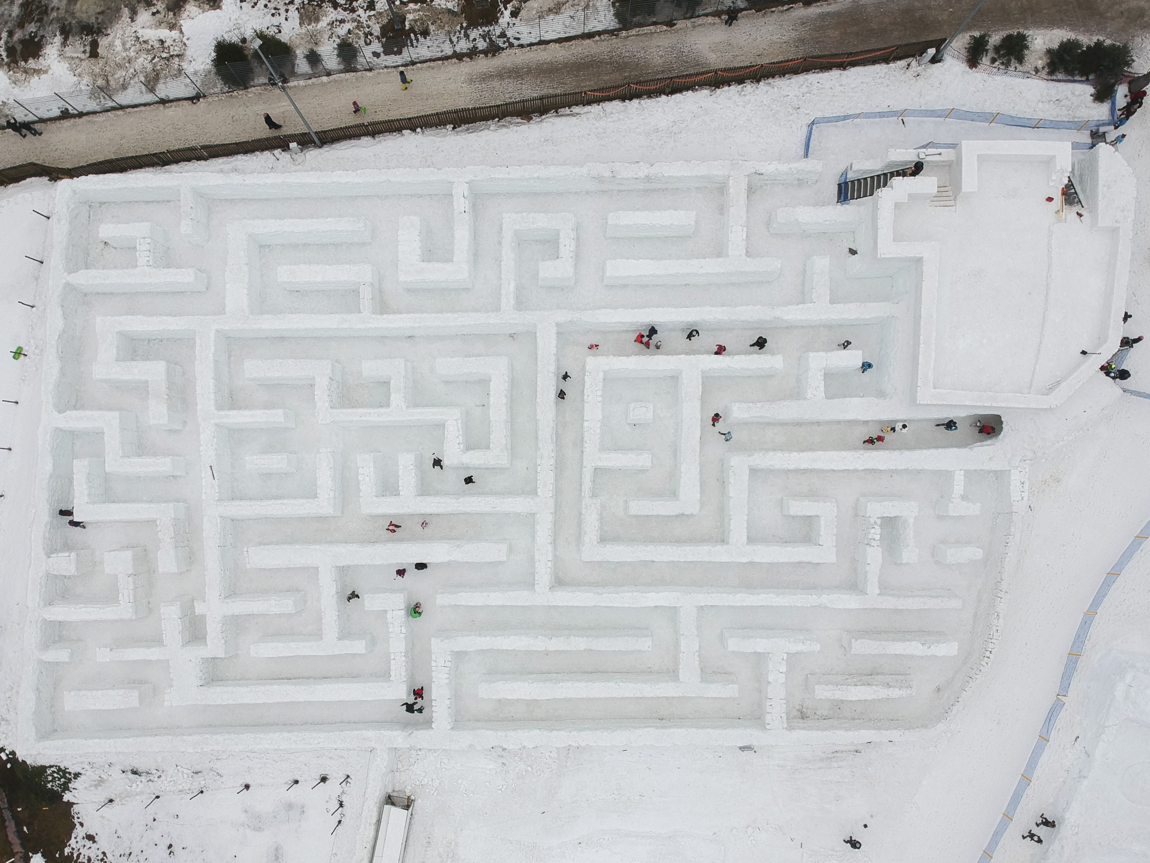 Slide 52 of 73: ZAKOPANE, POLAND JANUARY 11 : A drone view of visitors trying to find their way through the biggest snow maze of the world in Zakopane, Poland, January 11, 2018. The snow maze idea was created for the first time in the winter season of 2015/2016. Maze covers an area of 2500 square meters and it is considered as the biggest snow maze in the world. This season, the organization increased the size to 3000 square meters keeping its title for the biggest snow maze in the world.