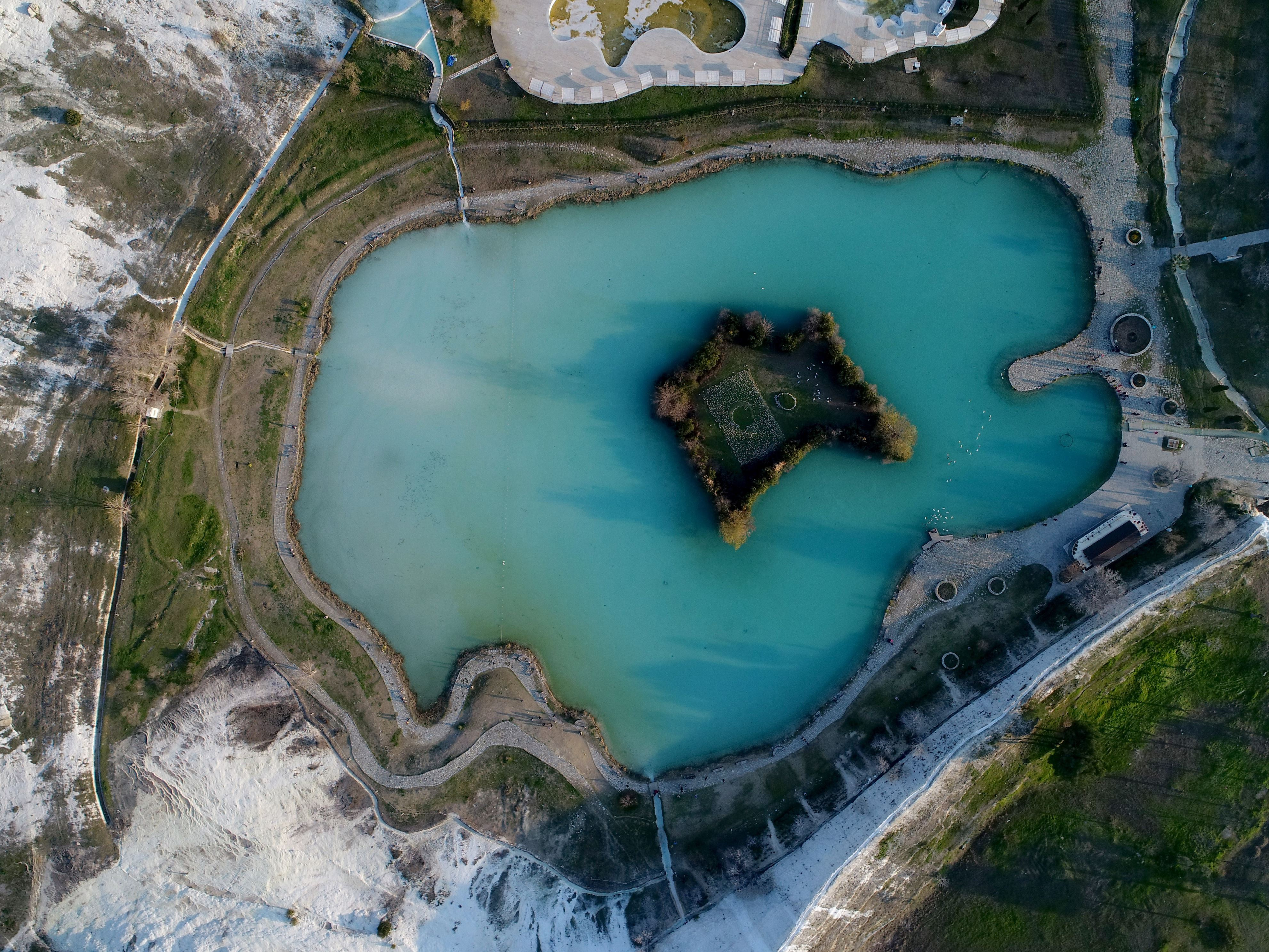 Slide 60 of 73: DENIZLI, TURKEY - JANUARY 6: A drone photo shows ancient city of Hierapolis and hot spring travertine pools and terraces at the UNESCO World Heritage Site of Pamukkale in Denizli, Turkey on January 6, 2017. Warm water at a temperature of 33-36 containing calcium hydro carbonate springing from 320 meters depth appears on the surface and water falls into terraces and forms the travertines.