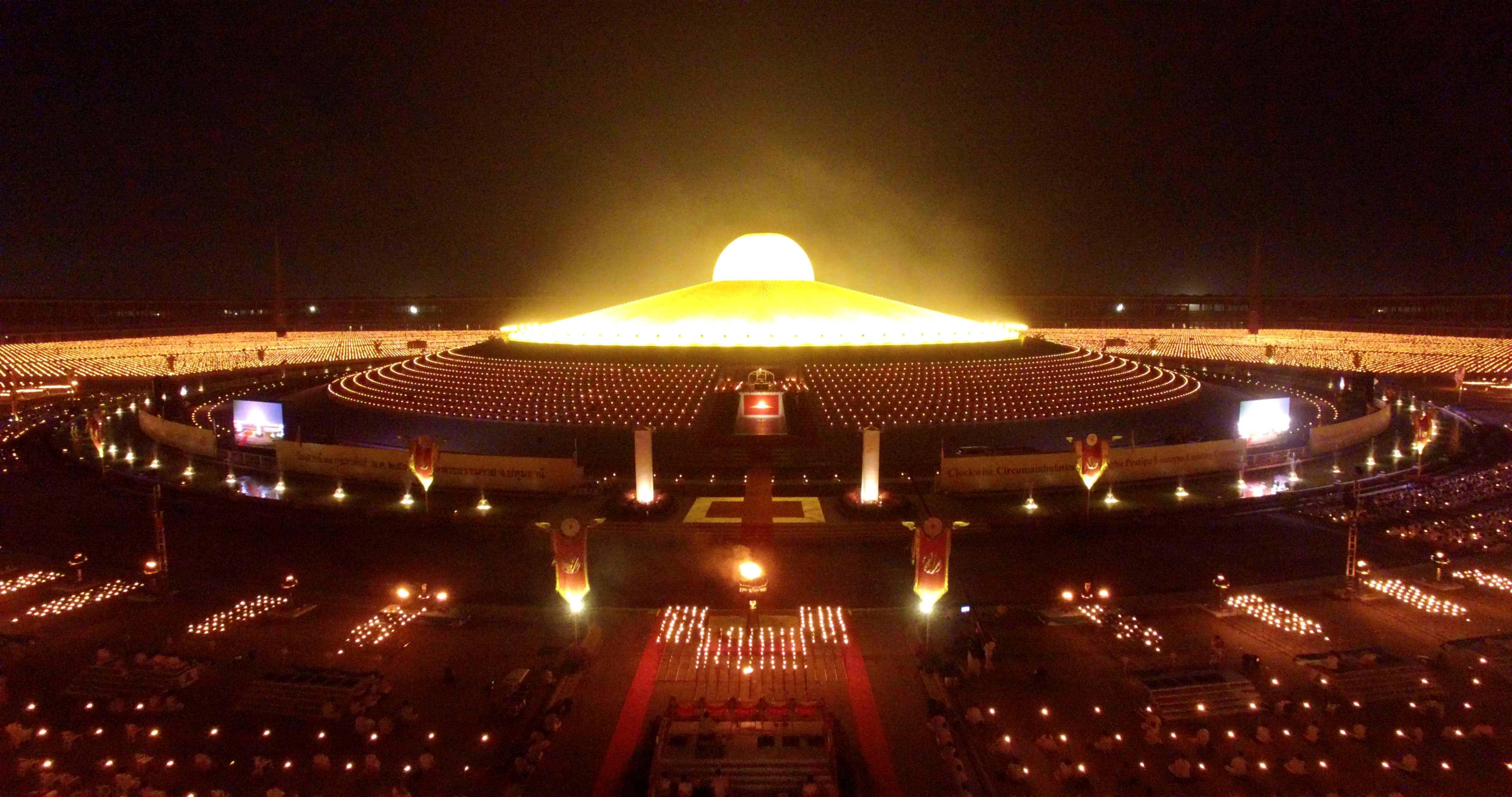 Slide 51 of 73: CAPTION: WAT DHAMAKAYA, BANGKOK, THAILAND - 2017/02/12: Image taken from a drone of thousands of Buddhist devotees and monks taking part in evening prayers by candlelight to mark Makha Bucha Day at Wat Dhammakaya temple, just north of Bangkok. Makha Bucha Day is held in celebration of the teachings of the Lord Buddha. (Photo by Stephen J. Boitano/LightRocket via Getty Images)