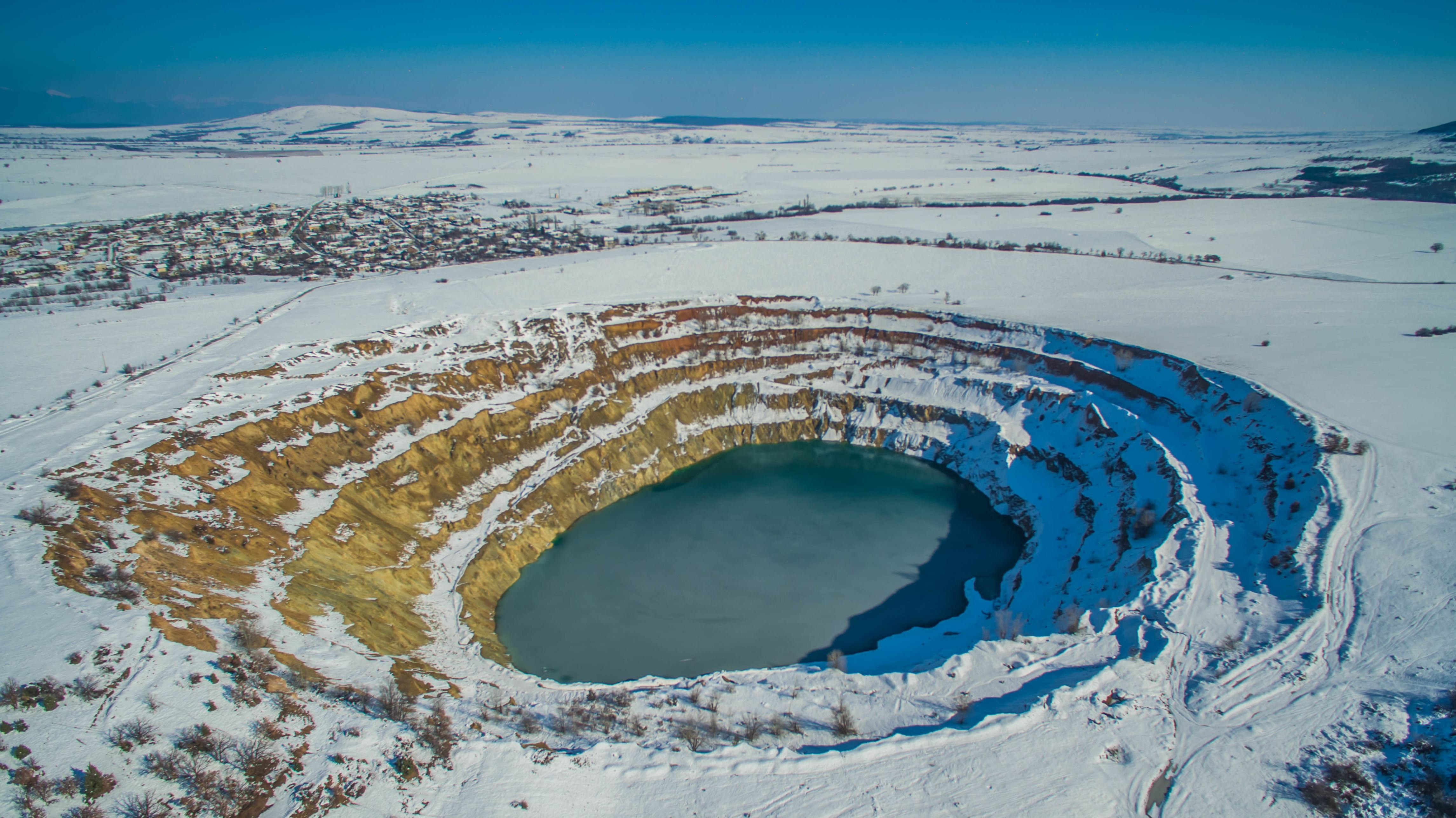 Slide 17 of 73: A drone view of snow covered and for the first time frozen abandoned copper mine located almost in the village of Tsar Asen (King Asen) at an elevation of about 300 m above sea levelel some 100 kms east of the Bulgaian capital Sofia, Wednesday, February, 03, 2016. Local residents near the mine and many supporters of former communist regime anounse it as a tourist attraction destination and many people mostly photographers visit it to photograph the unique green water on the bottom of the mine. Just near the mine a infield is also located. Photo by: Petar Petrov/Impact Press Group/NurPhoto (Photo by NurPhoto/NurPhoto via Getty Images)