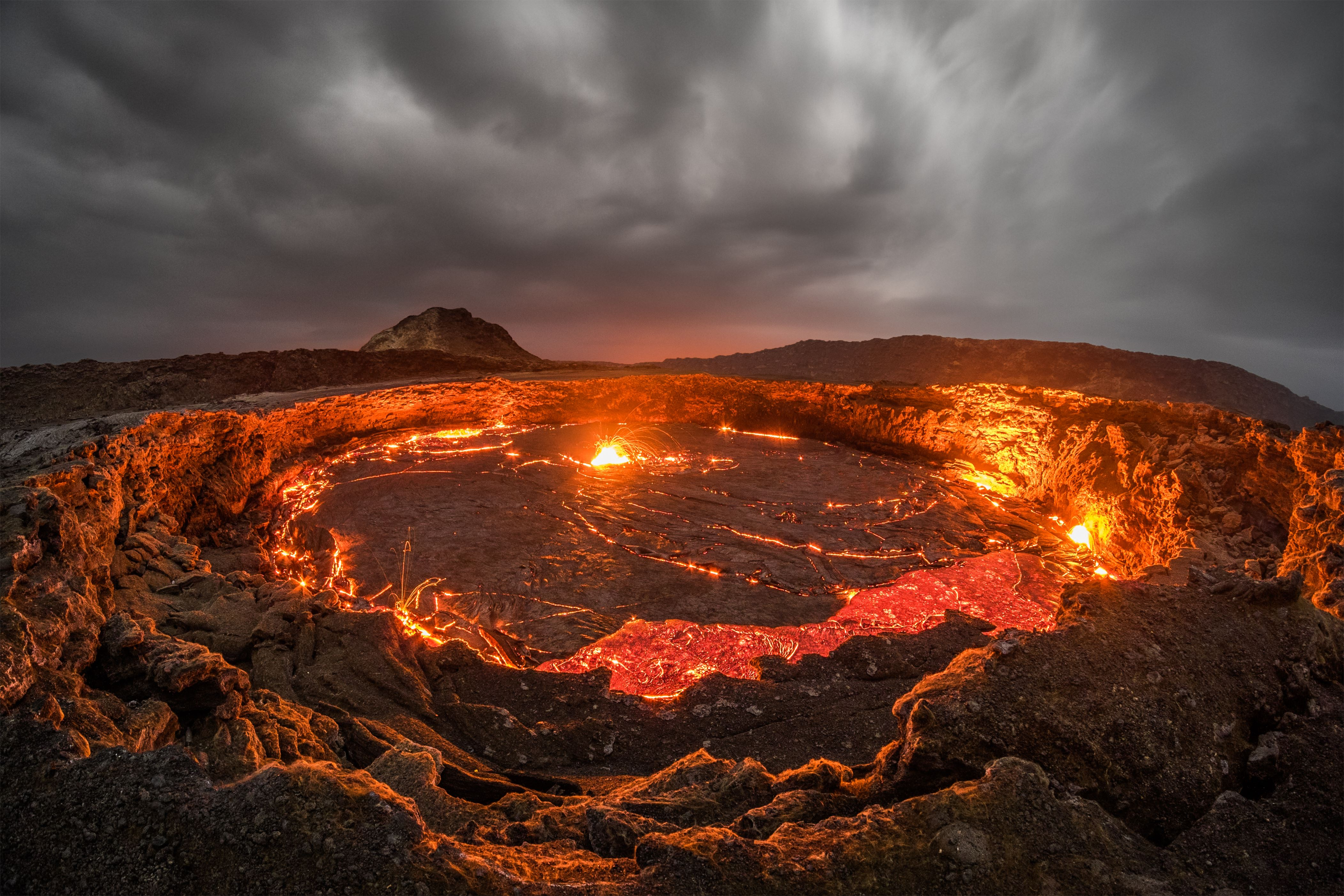 Slide 66 of 73: *** EXCLUSIVE - VIDEO AVAILABLE *** ETHIOPIA - JANUARY 10: Lava rising on top of the surface of the Erta Ale volcano lava lake on January 10, 2015 in Ethiopia. THESE fiery images offer a glimpse inside the 'Gateway To Hell' - the worlds oldest continuously active lava lake. Travel photographer Joel Santos, 38, piloted a drone low over the bubbling lake, which reaches temperatures exceeding 1,100 degrees celsius. The lake, which has had a continuous flow since 1906, is situated inside the Erta Ale volcano, otherwise known as Smoking Mountain, in the Afar region of northeastern Ethiopia. The volcanos last major eruption occurred in 2005, killing 250 livestock and forcing thousands of nearby residents to flee. And the Portuguese photographer remained acute aware of the hazards posed by filming such a potentially devastating natural phenomenon at such close quarters. PHOTOGRAPH BY Joel Santos / Barcroft Images London-T:+44 207 033 1031 E:hello@barcroftmedia.com - New York-T:+1 212 796 2458 E:hello@barcroftusa.com - New Delhi-T:+91 11 4053 2429 E:hello@barcroftindia.com www.barcroftimages.com (Photo credit should read Joel Santos / Barcroft Images / Barcroft Media via Getty Images)