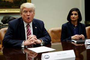 Administrator of the Centers for Medicare and Medicaid Services Seema Verma listens at right as President Donald Trump speaks