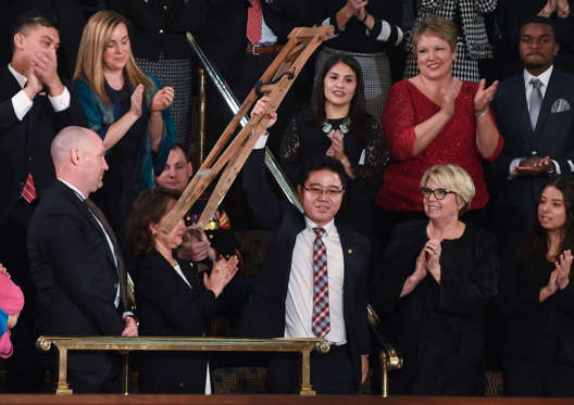 Slide 3 of 31: North Korean defector Ji Seong-ho raises his crutches as US President Donald Trump delivers the State of the Union address at the US Capitol in Washington, DC, on January 30, 2018. / AFP PHOTO / SAUL LOEB (Photo credit should read SAUL LOEB/AFP/Getty Images)