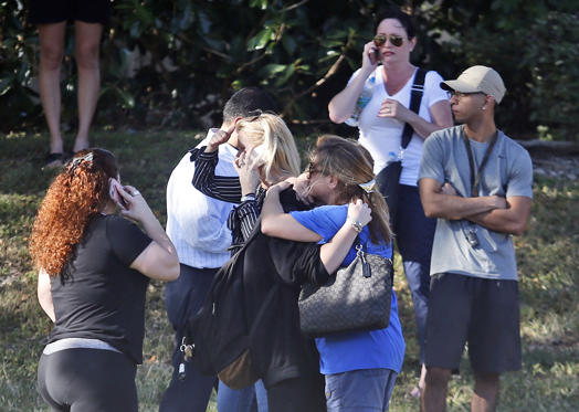Slide 3 of 11: Anxious family members wait for news of students as two people embrace, Wednesday, Feb. 14, 2018, in Parkland, Fla. A shooting at Marjory Stoneman Douglas High School sent students rushing into the streets as SWAT team members swarmed in and locked down the building.