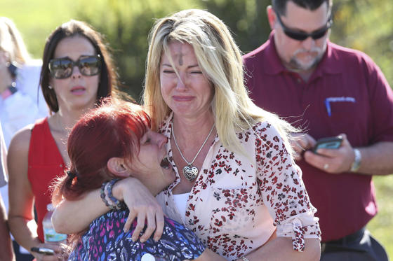 Slide 1 of 11: Parents wait for news after a reports of a shooting at Marjory Stoneman Douglas High School in Parkland, Fla., on Wednesday, Feb. 14, 2018.