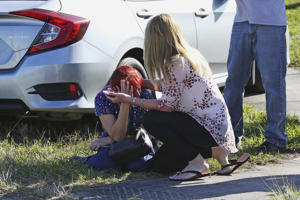 A woman consoles another as parents wait for news regarding a shooting at Marjory Stoneman Douglas High School in Parkland, Fla., Wednesday, Feb. 14, 2018. A shooter opened fire at the Florida high school Wednesday, killing people, sending students running out into the streets and SWAT team members swarming in before authorities took the shooter into custody.