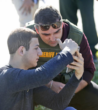 Slide 2 of 11: A student shows a law enforcement officer a photo or video from his phone, Wednesday, Feb. 14, 2018, in Parkland, Fla. A shooting at Marjory Stoneman Douglas High School sent students rushing into the streets as SWAT team members swarmed in and locked down the building. Police were warning that the shooter was still at large even as ambulances converged on the scene and emergency workers appeared to be treating those possibly wounded.