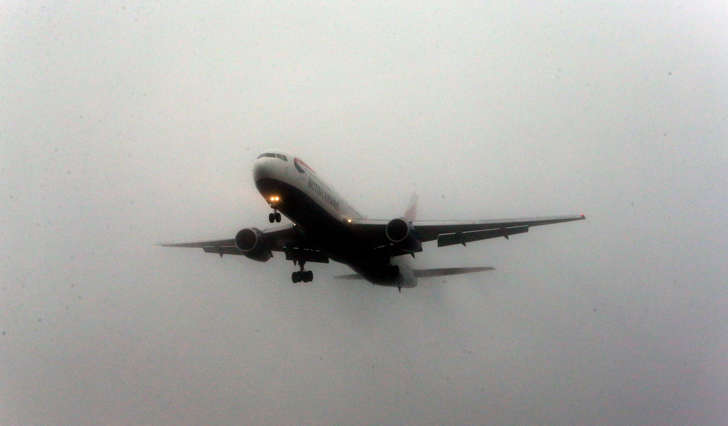 A plane lands in the fog at Heathrow Airport as early-morning fog disrupted flights