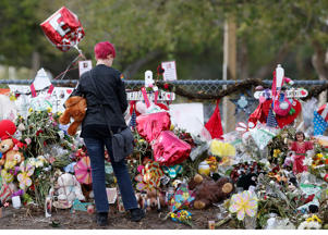 A Marjory Stoneman Douglas High School student stops to look at one of the memorials following their return to school in Parkland, Florida on February 28, 2018. A former student, Nikolas Cruz, opened fire at Marjory Stoneman Douglas High School leaving 17 people dead and 15 injured on February 14. Students grieving for slain classmates prepared for an emotional return Wednesday to their Florida high school, where a mass shooting shocked the nation and led teen survivors to spur a growing movement to tighten America's gun laws. The community of Parkland, Florida, where residents were plunged into tragedy two weeks ago, steeled itself for the resumption of classes at Marjory Stoneman Douglas High School, where nearby flower-draped memorials and 17 white crosses pay tribute to the 14 students and three staff members who were murdered by a former student.  / AFP PHOTO / RHONA WISE        (Photo credit should read RHONA WISE/AFP/Getty Images)
