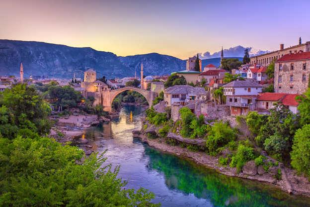 Διαφάνεια 6 από 51: The Neretva river winding through the old UNESCO listed, Mostar bridge in Bosnia and Herzegovina.