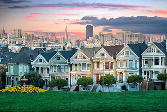 Slide 2 of 24: San Francisco cityscape with the Painted Ladies as seen from Alamo square park.