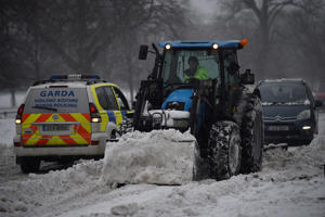 A digger tractor and Irish police help remove snow from the road in Dublin, Ireland, March 2, 2018. REUTERS/Clodagh Kilcoyne