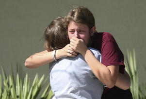 Students grieve outside Pines Trail Center where counselors are present, after Wednesday's mass shooting at Marjory Stoneman Douglas High School in Parkland, Fla., Thursday, Feb. 15, 2018. Nikolas Cruz was charged with 17 counts of premeditated murder Thursday morning.