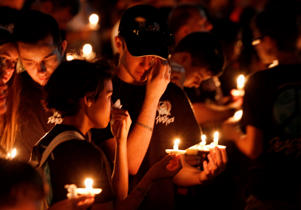 Thousands of mourners hold candles a candlelight vigil for victims of the Marjory Stoneman Douglas High School shooting in Parkland, Florida on February 15, 2018. A former student, Nikolas Cruz, opened fire at the Florida high school leaving 17 people dead and 15 injured. / AFP PHOTO / RHONA WISE (Photo credit should read RHONA WISE/AFP/Getty Images)