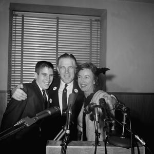 "Industrialist George Romney gave his wife Lenore and son Mitt, 14, an affectionate hug for the benefit of photographers at a Detroit news conference February 10, 1962 after he announced he would seek the Republican nomination for Governor of Michigan. Romney said he would not become an active candidate until ""Completion of my responsibilities as a delegate to the constitutional convention."" (AP Photo)."