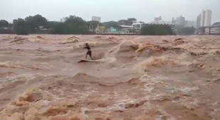 Surfer rides waves in overflowing river