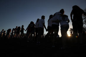 Students and family members holds hands around a makeshift memorial in front of Marjory Stoneman Douglas High School where 17 people were killed on February 14, on February 18, 2018 in Parkland, Florida. Police arrested 19-year-old former student Nikolas Cruz for killing 17 people at the high school.