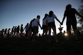 Students and family members holds hands around a makeshift memorial in front of Marjory Stoneman Douglas High School where 17 people were killed on February 14, on February 18, 2018 in Parkland, Florida. (file photo)