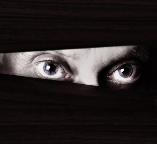 Black and white close up of sinister-looking male eyes looking suspiciously  through the slats of a closed  venetian blind. Could be a criminal or a stalker or a watchful home owner. Ample copy space on the dark blind.