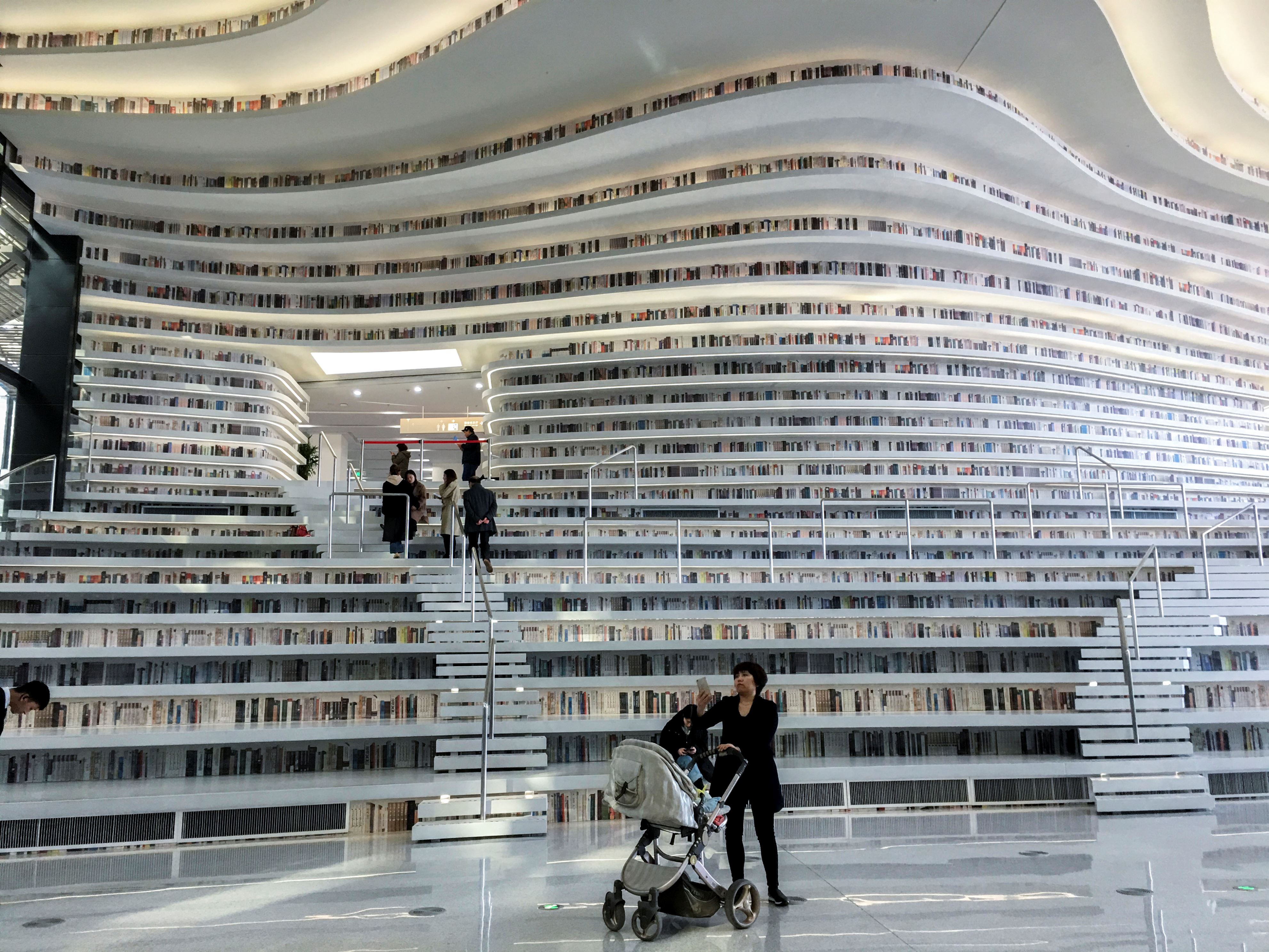 Slide 48 of 57: CAPTION: TIANJIN, CHINA - 2018/03/05: With a huge spherical multi-function hall and circle steps to the ceiling, Tianjin Binhai new area library is now a popular topic on social media and a new tourist attraction of this city, also called 'the most beautiful library in China'. (Photo by Zhang Peng/LightRocket via Getty Images)