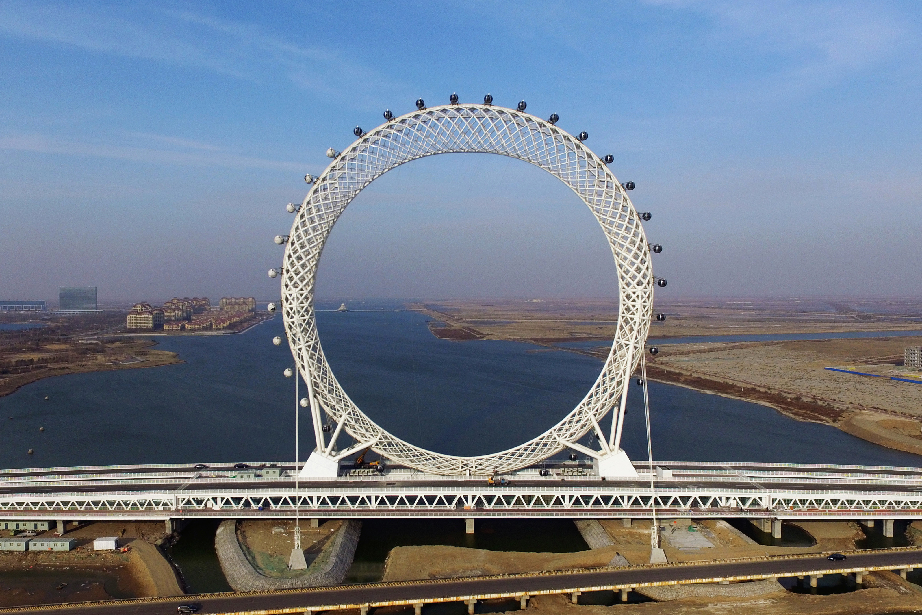 Slide 47 of 57: CAPTION: This photo taken on November 27, 2017 shows a 145-metre (476 feet) high spokeless ferris wheel in Weifang in China's eastern Shandong province. The ferris wheel is made up of 36 pods that can carry 10 passengers each. / AFP PHOTO / - / China OUT (Photo credit should read -/AFP/Getty Images)