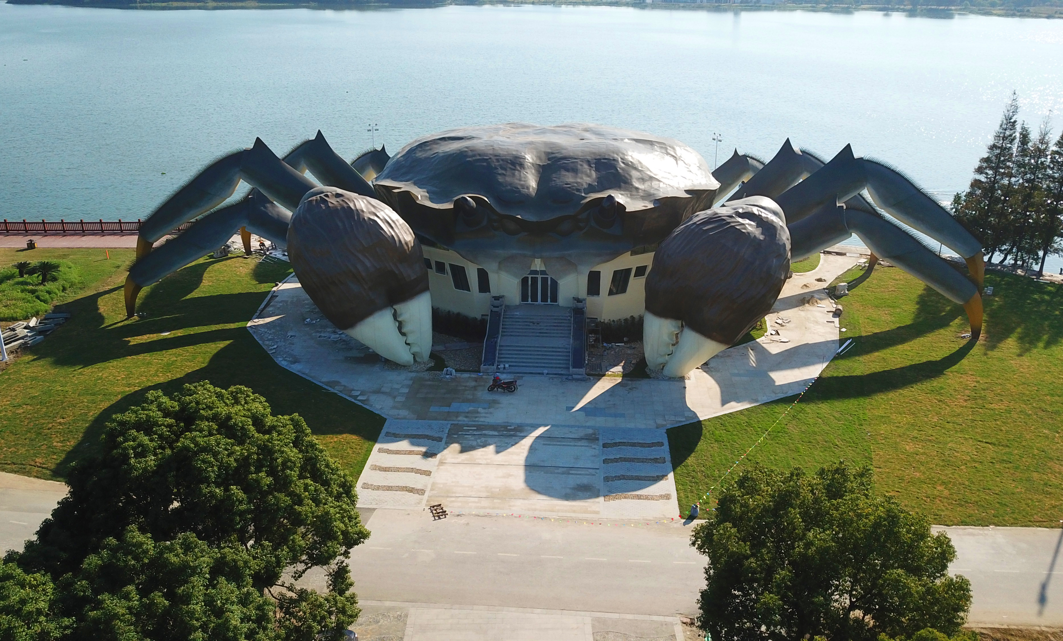 Slide 46 of 57: CAPTION: SUZHOU, CHINA - OCTOBER 31: Aerial view of a crab-shaped eco museum under construction on the shore of Yangcheng Lake on October 31, 2017 in Suzhou, Jiangsu Province of China. The crabs produced in Yangcheng Lake have long enjoyed great reputation abroad, and are sometimes known as 'Chinese Mitten Crabs'. The stainless steel exo museum is 75 meters long and 16 meters high with three floors in all, which will provide residents a place for recreation and leisure after completion. The construction work is still under way and it is expected to open in the second half of the next year. (Photo by VCG/Getty Images)