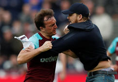 "Soccer Football - Premier League - West Ham United vs Burnley - London Stadium, London, Britain - March 10, 2018   West Ham United's Mark Noble clashes with a fan who has invaded the pitch    Action Images via Reuters/Peter Cziborra    EDITORIAL USE ONLY. No use with unauthorized audio, video, data, fixture lists, club/league logos or ""live"" services. Online in-match use limited to 75 images, no video emulation. No use in betting, games or single club/league/player publications.  Please contact your account representative for further details."