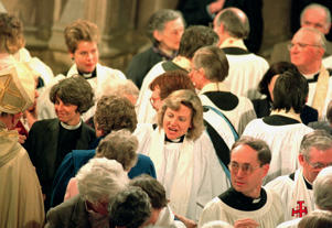 The first woman priest of the Church of England, the Reverand Angela Berners-Wilson joins the rest of the congregation after the ordination of women priests at Bristol Cathedral.
