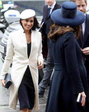 Meghan Markle smiles at the Duchess of Cambridge