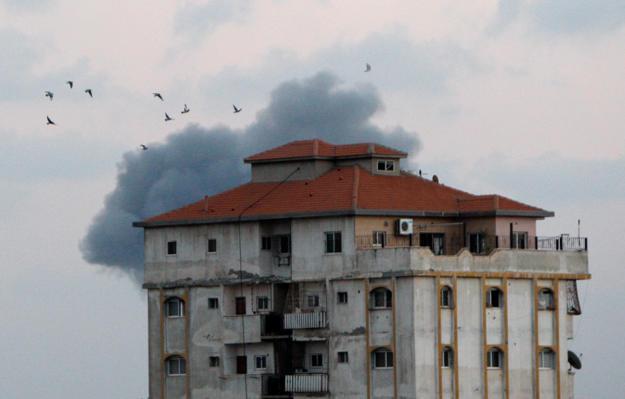 Smoke rises as birds fly following an Israeli air strike in Gaza City July 20, 2018. REUTERS/Ahmed Zakot