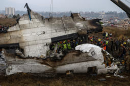 KATHMANDU, NEPAL - MARCH 12: Nepali rescue workers gather around the debris of an airplane that crashed near the international airport in Kathmandu on March 12, 2018. At least 49 passengers were killed and 22 others wounded after a passenger aircraft of a private Bangladeshi airline skidded off the runway and caught fire in capital Kathmandu, according to police. (Photo by Sunil Pradhan/Anadolu Agency/Getty Images)