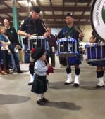 Toddler plays along with bagpipe band