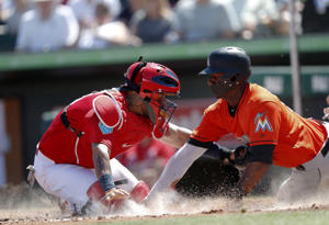 Miami Marlins' Lewis Brinson (9) is tagged out by St. Louis Cardinals catcher Yadier Molina (4) as he tries to score on a Miguel Rojas base hit in the fifth inning of a spring training baseball game Friday, March 16, 2018, in Jupiter, Fla.